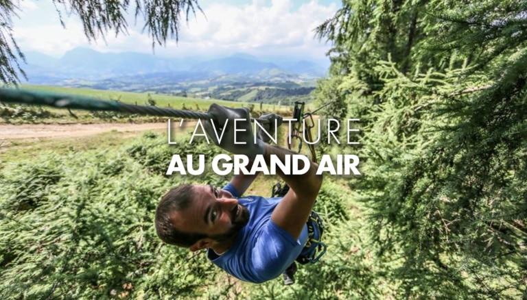 Homme souriant en train de descendre en tyrolienne dans un parc aventure en Béarn