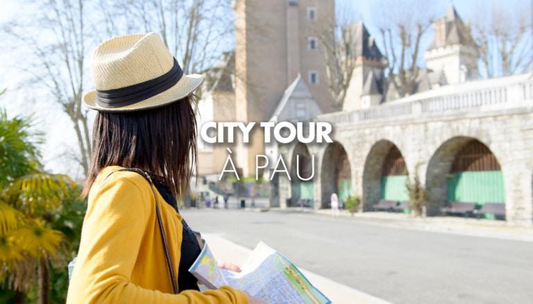 Personne tenant une carte de Pau devant le Château de Pau